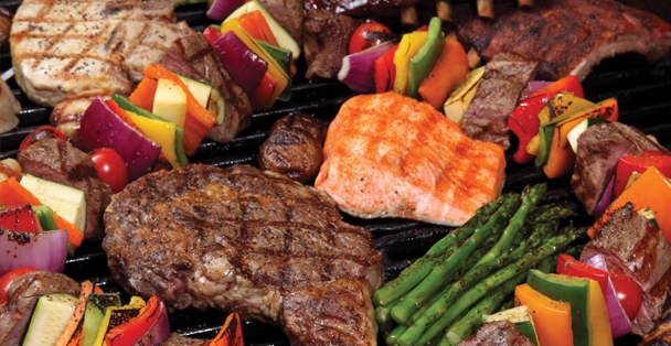 A variety of barbecued meat and vegetables on a grill.